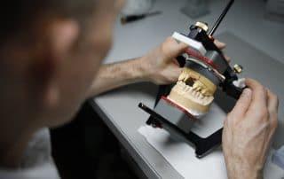 Zahntechniker arbeitet an einem Modell